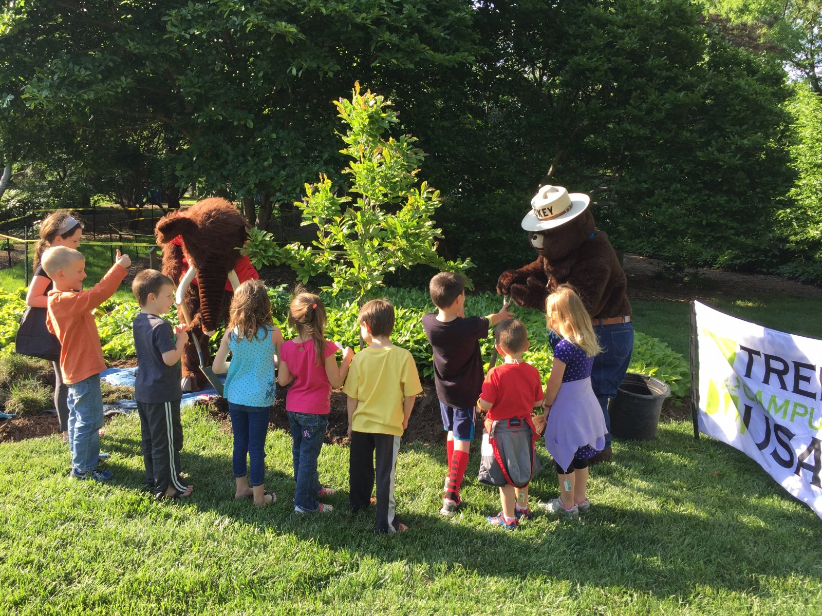 Children gather around newly planted tree and Smokey bear.