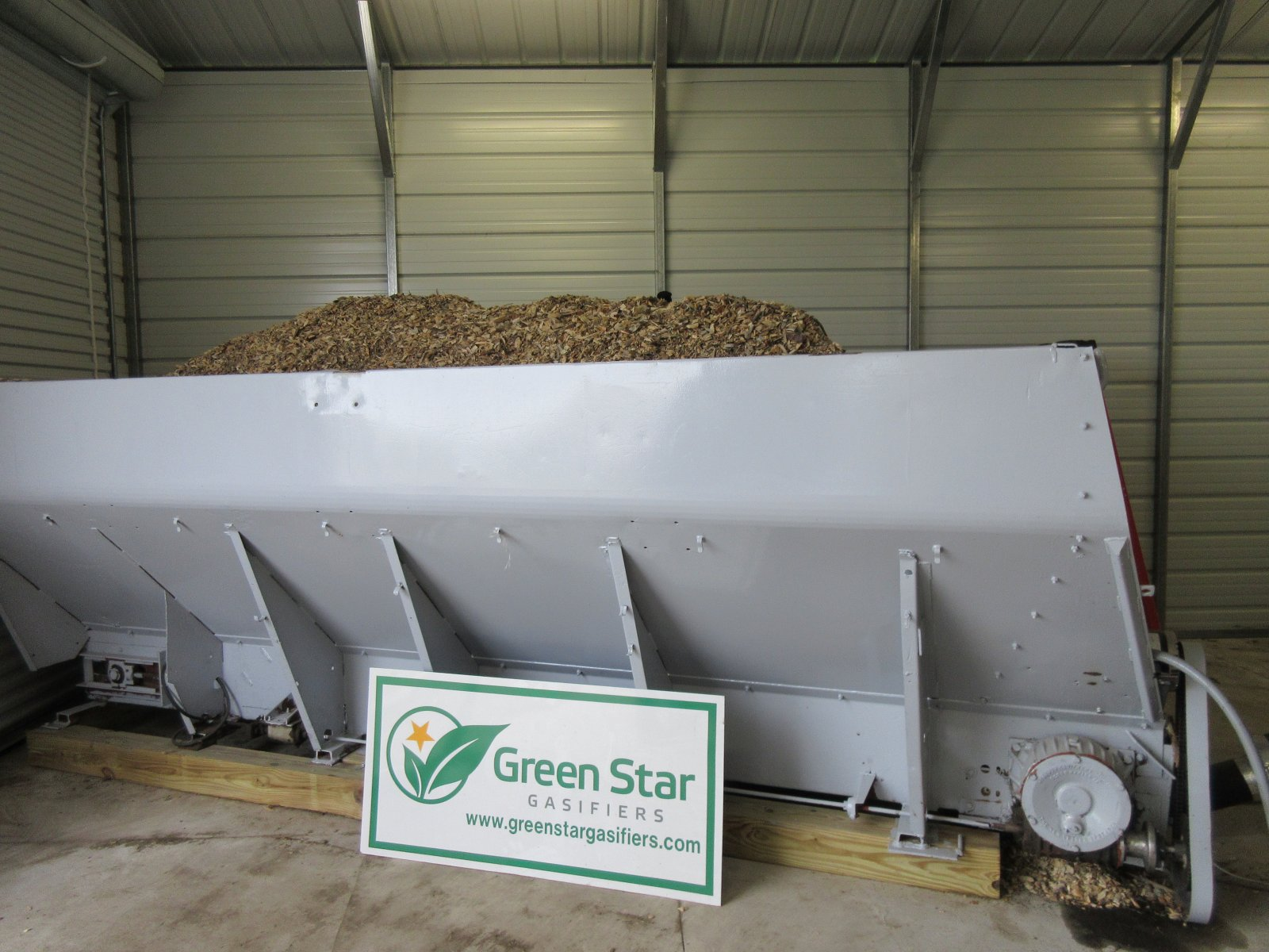Wood chips are piled into machine that creates electricity.