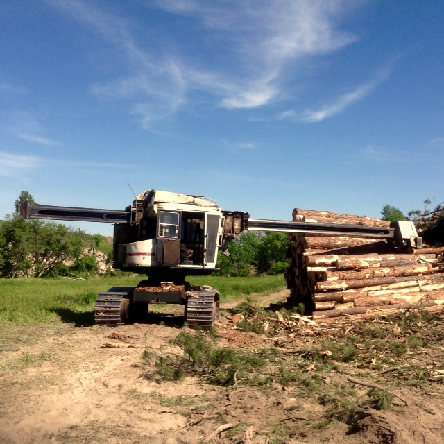 Machine harvesting timber logs in Nebraska forest