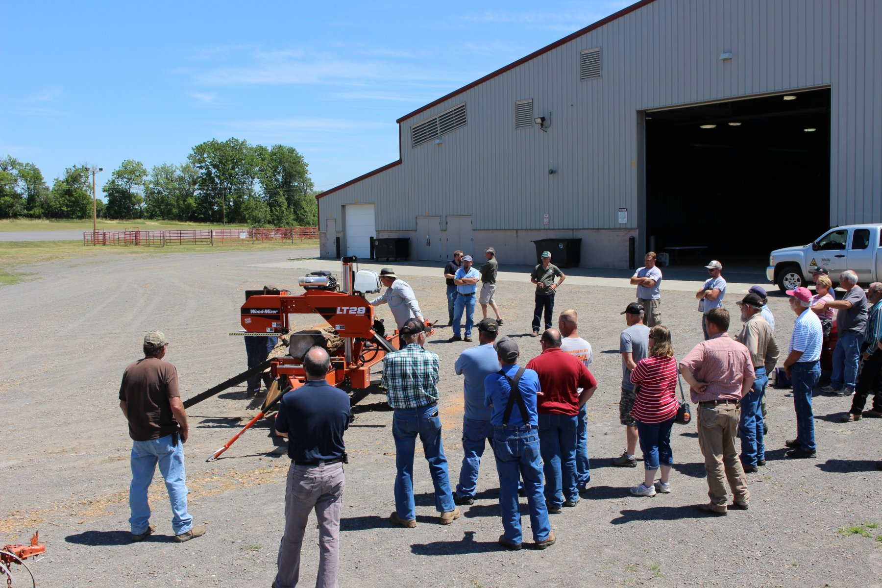 Patrons gathered around a portable sawmil demonstration.