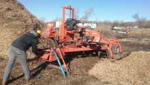 Portable sawmill processing ash log.
